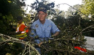 Florida Gov. Rick Scott picks up fallen branches to put into the back of a truck Wednesday, Sept. 7, 2016 during a debris cleanup from Hurricane Hermine in Indian Head Acres in Tallahassee, Fla. (AP Photo/Phil Sears)