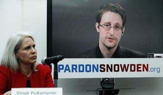 Dinah PoKempner, general council for Human Rights Watch, listens Wednesday in New York as Edward Snowden speaks on a television screen via video link from Moscow during a news conference to call upon President Obama to pardon Snowden before he leaves office. (Associated Press)