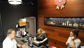 Scott Schwar, left, of Oak Park, Il, orders the first cocktail at the new Jim Beam Bourbon Bar located on the grounds of the Jim Beam Distillery, Wednesday, Sept. 14, 2016, in Clermont, Ky. This summer, Kentucky passed legislation allowing distilleries to apply for licenses to permit the sale of cocktails by the glass, and Jim Beam was among the first to receive it's license. (AP Photo/Timothy D. Easley)
