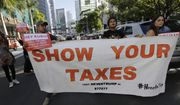 Protestors march in a downtown street holding a sign in support of Republican presidential candidate Donald Trump releasing his tax returns, outside of a campaign rally attended by Trump, Friday, Sept. 16, 2016, in Miami. (AP Photo/Lynne Sladky) ** FILE **