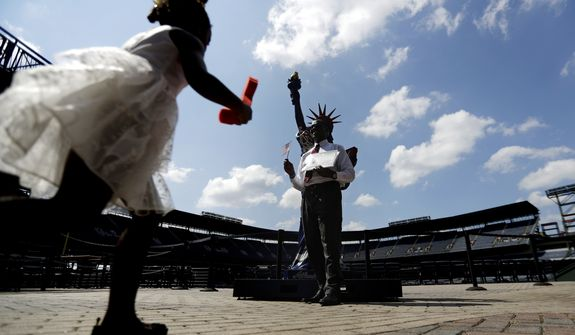 Nia Mwangi, 5, runs to join her father Eric Mwangi, of Kenya, in a photo with a Statue of Liberty on display following a naturalization ceremony for 755 new United States citizens at Turner Field, home of the Atlanta Braves baseball team in Atlanta, Friday, Sept. 16, 2016. The ceremony, in honor of Constitution Day and Citizenship Day, was the largest in Georgia this year and the 755 citizens sworn in marks the number of home runs hit by former Braves player Hank Aaron. (AP Photo/David Goldman)