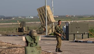 An Israeli soldier guards an Iron Dome air defense system in the Golan Heights near the border with Syria. From across the frontier, the sounds of war are ever present. (Associated Press)