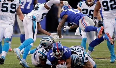 FILE - In this Dec. 20, 2015, file photo, New York Giants' Odell Beckham (13) hits Carolina Panthers' Josh Norman (24) after teammate Shane Vereen (34) was tackled by Kurt Coleman (20) and Roman Harper (41) during the second half of an NFL football game Sunday, Dec. 20, 2015, in East Rutherford, N.J. Beckham, involved in a game-long helmet-smacking, shoving and jawing session with Norman, scored the tying touchdown with 1:46 left in the Giants' 38-35 loss to Carolina. The question for the NFL is why was OBJ still in the game after losing his cool so many times as Norman was getting the best of him in their high-profile matchup. (AP Photo/Julie Jacobson, File)