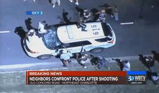 In this frame from video provided by WBTV, a police vehicle is damaged after protests broke out Tuesday, Sept. 20, 2016, in Charlotte, N.C., following a fatal shooting of a black man by police. (WBTV via AP)