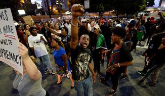 Protesters block an intersection near the Transit Center as they march uptown in Charlotte, N.C. Wednesday, Sept. 21, 2016. Authorities in Charlotte tried to quell public anger Wednesday after a police officer shot a black man, but a dusk prayer vigil turned into a second night of violence, with police firing tear gas at angry protesters and a man being critically wounded by gunfire. North Carolina's governor declared a state of emergency in the city. (Jeff Siner/The Charlotte Observer via AP)