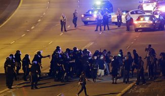 Police confront protesters blocking I-277 during a third night of unrest following Tuesday's police shooting of Keith Lamont Scott in Charlotte, N.C., Thursday, Sept. 22, 2016. (AP Photo/Gerry Broome)