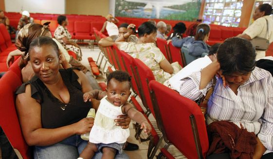 In this Thursday, Jan. 21, 2010, file photo, Haitian national Carole Manigat, left, holds her daughter Hadassa Carole Albert as she waits for her turn to fill out temporary protective status papers at Notre Dame d'Haiti Catholic Church in the Little Haiti neighborhood in Miami. (AP Photo/Alan Diaz, File)