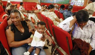 In this Thursday, Jan. 21, 2010, file photo, Haitian national Carole Manigat, left, holds her daughter Hadassa Carole Albert as she waits for her turn to fill out temporary protective status papers at Notre Dame d'Haiti Catholic Church in the Little Haiti neighborhood in Miami. The U.S. Department of Homeland Security said Thursday, Sept. 22, 2016, that it was widening efforts to deport Haitians, a response to thousands of immigrants from the Caribbean nation who have overwhelmed California border crossings with Mexico in recent months. The move lifts special protections that shielded Haitians from deportation after their nations 2010 earthquake. (AP Photo/Alan Diaz, File)