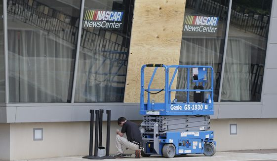 A plywood board cover a broken glass panel at the NASCAR Hall of Fame after a second night of violence following Tuesday's fatal police shooting of Keith Lamont Scott in Charlotte, N.C. Thursday, Sept. 22, 2016. (AP Photo/Chuck Burton)