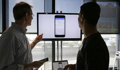 LinkedIn principal NLP scientist and senior product manager Dan Bikel, left, and engineering manager Amol Neurgaonkar demonstrate new messaging features after a product announcement at LinkedIn's headquarters, Thursday, Sept. 22, 2016, in San Francisco. (AP Photo/Eric Risberg)