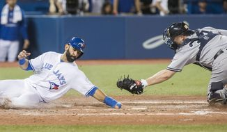 Toronto Blue Jays' Jose Bautista, left, comes in to score past New York Yankees catcher Brian McCann during the seventh inning of a baseball game in Toronto, Friday, Sept. 23, 2016. (Mark Blinch/The Canadian Press via AP)