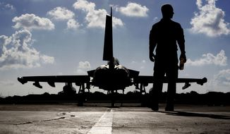 In this Thursday, Sept. 22, 2016 photo, a British soldier walks by a Typhoon aircraft before take off for a mission in Iraq, at  RAF Akrotiri, near the southern coastal city of Limassol, in Cyprus.  British Tornado and Typhoon aircraft stationed at a U.K. air base in Cyprus are pounding Islamic State targets ahead of a major offensive by Iraqi security forces next month to recapture the key northern city of Mosul from IS militants, a senior Royal Air Force officer says. (AP Photo/Petros Karadjias, Pool)