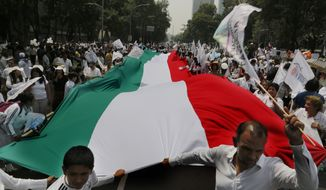 Demonstrators walk with a giant Mexican national flag during a march organized by representatives of the National Front for the Family, in Mexico City, Saturday, Sept. 24, 2016. Dueling marches, in support and against Mexican President Enrique Pena Nietos push to legalize same-sex marriage, gathered at the Angel of Independence monument. The two sides were kept apart Saturday by hundreds of police and barriers erected around the city's iconic monument. (AP Photo/Marco Ugarte