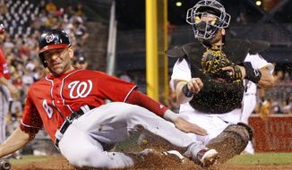 Washington Nationals' Danny Espinosa, left, scores as the ball gets away from Pittsburgh Pirates catcher Francisco Cervelli in the fourth inning of a baseball game in Pittsburgh, Saturday, Sept. 24, 2016. Espinosa scored on a fielder's choice by Jayson Werth. (AP Photo/Gene J. Puskar)