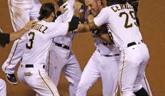 Pittsburgh Pirates' Jacob Stallings, center, celebrates with teammates after hitting a walk-off bases loaded single off Washington Nationals relief pitcher Yusmeiro Petit in the 11th inning a baseball game in Pittsburgh, Friday, Sept. 23, 2016. The Pirates won 6-5. (AP Photo/Gene J. Puskar)