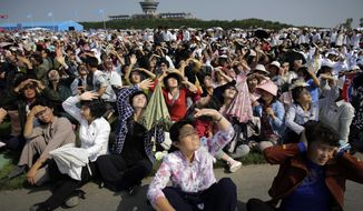 North Koreans shield their eyes from the sun as they watch an aerial display on Saturday, Sept. 24, 2016, in Wonsan, North Korea. North Korea on Saturday opened an air festival featuring sky diving, demonstrations by its air force and lots of beer to promote a newly renovated and upgraded commercial airport in the coastal city of Wonsan that it hopes will draw for foreign tourists. (AP Photo/Wong Maye-E)