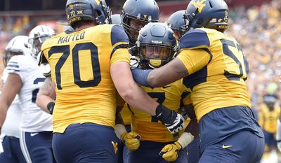 West Virginia running back Rushel Shell (7) celebrates his touchdown with offensive linemen Tony Matteo (70) and Adam Pankey (57) during the first half of an NCAA college football game against BYU, Saturday, Sept. 24, 2016, in Landover, Md. (AP Photo/Nick Wass)