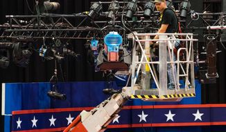 A technician examines the lighting grid as preparations continue for Monday's first debate presidential between Democratic Hillary Clinton and Republican Donald Trump, Saturday, Sept. 24, 2016, at Hofstra University in Hempstead, N.Y.  (AP Photo/J. David Ake)