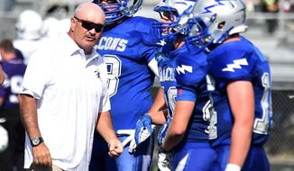 ADVANCE FOR THE WEEKEND OF SEPT 24-25 AND THEREAFTER - In this Aug. 26, 2016 photo, Billings Skyview defensive coordinator Rich St. John, left, chats with some of his players during a time out in the season opener against Butte in Billings, Mont. St. John has been with the Billings Department since 1981 and police chief since 2005.  He is also an assistant coach for the Billings Skyview football team  (Hannah Potes/The Billings Gazette via AP)