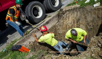 FILE- In a file photo form Aug. 31, 2016, crews break ground and work to remove and replace lead-tainted pipes from three homes during first day of the second phase under Mayor Karen Weaver's Fast Start program Wednesday, in Flint, Mich. A year after Flint's water crisis broke open, its residents still do have not water that is safe to drink without a filter. The replacement of lead pipes is slow. The Associated Press breaks down where things stand on various facets of the man-made public health disaster _ criminal charges, lawsuits, the transition to a new water pipeline, state aid, economic development efforts and other initiatives. (Jake May/The Flint Journal-MLive.com via AP)    /The Flint Journal-MLive.com via AP)