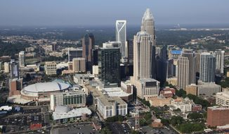 FILE - In this Aug. 16, 2012 file photo, the Time Warner Cable Arena is shown on left of downtown Charlotte, N.C.    To much of the world, Charlotte is the Queen City, a gleaming downtown, state-of-the-art stadiums, sparkling new mass transit, the nation's banking capital. But a very different Charlotte came into the spotlight in the past few days. Move outside the city's core and there are neighborhoods like the one where a white police officer shot and killed a black man, Keith Scott, Sept. 20, 2016, setting off violent protests.(AP Photo/Chuck Burton)
