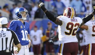 New York Giants quarterback Eli Manning (10) and Washington Redskins' Chris Baker (92) react after Manning threw an interception during the second half of an NFL football game Sunday, Sept. 25, 2016, in East Rutherford, N.J. (AP Photo/Bill Kostroun)