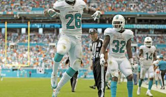 Miami Dolphins running back Damien Williams (26) celebrates in the end zone after scoring in the fourth quarter as the Miami Dolphins beat the Cleveland Browns in the home opener at refurbished Hard Rock Stadium on Sunday, Sept. 25, 2016. (Al Diaz/Miami Herald via AP)