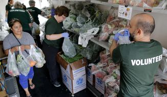 In this Sept. 22, 2016 photo, volunteers hand out fresh produce to a woman inside a refrigerator truck at Oak Forest Health Center in Oak Forest, Ill. Six health clinics are working with the Chicago food bank to host a mobile pantry filled with fresh produce. The clinics have hosted 26 'Fresh Truck' visits with the Greater Chicago Food Depository since last year, providing more than 100,000 pounds of fresh fruits and vegetables to more than 3,200 households. (AP Photo/Tae-Gyun Kim)