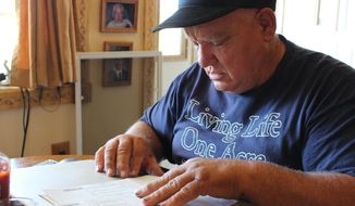 In this  Sept. 15, 2016, photo, Jan Brown looks over a royalty statement at his home in Wyalusing, Pa. Brown and other landowners with natural gas wells contend that gas companies are ripping them off by taking improper deductions from their royalty checks. The drilling industry says the deductions are proper. (AP Photo/Michael Rubinkam)