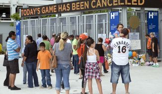 Fans of the Miami Marlins come an pay their respect, Sunday, Sept. 25, 2016, to Marlins pitcher Jose Fernandez as the game against the Atlanta Braves was canceled. Jose Fernandez, the ace right-hander for the Miami Marlins who escaped Cuba to become one of baseball's brightest stars, was killed in a boating accident early Sunday. Fernandez was 24. (AP Photo/Gaston De Cardenas)