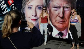 Students pose for photographs near the presidential debate between presidential candidates Hillary Clinton and Donald Trump at Hofstra University on Monday in Hempstead, New York. (Associated Press)