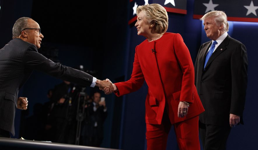 Hillary Clinton shakes hands with moderator Lester Holt as Donald Trump looks on at the first presidential debate Monday at Hofstra University in Hempstead, New York. (Associated Press)