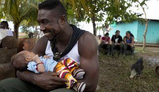 Diomedes holds the baby of a visiting relative of a fellow rebel of the Revolutionary Armed Forces of Colombia, FARC, in the Yari Plains, southern Colombia, Sunday, Sept. 25, 2016. President Juan Manuel Santos and FARC leader Rodrigo Londono, alias Timochenko, are expected to sign a peace accord to end more than five decades of conflict Sept. 26 in the Caribbean city of Cartagena. (AP Photo/Ricardo Mazalan)
