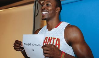 Atlanta Hawks center Dwight Howard holds up a sign with his name and number before having his photo taken by a photographer during the NBA basketball team's media day Monday, Sept. 26, 2016, in Atlanta. The Hawks are set to show off a new look that includes Howard and Dennis Schroder in their starting five. (AP Photo/John Bazemore)