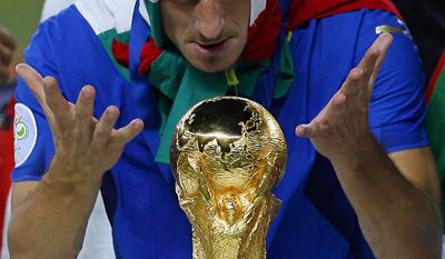 FILE - In this photo from files taken on July 9, 2006, Italy's Francesco Totti looks at the World Cup trophy after the final of the soccer World Cup between Italy and France in the Olympic Stadium in Berlin. Totti celebrates his 40th birthday on Tuesday, Sept. 27, 2016,  but is showing no signs of slowing down and indeed seems to have found a new lease of life. He may not be Roma's 'Golden Boy' anymore but he is still very much 'the King of Rome.'   (AP Photo/Jasper Juinen, file)
