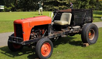 The golf course tractor made famous in a series of commercials for motor oil by golf legend Arnold Palmer sits next to a tee box during a golf putting at the the course Palmer grew up on, the Latrobe Country Club, in Unity, Pa., Monday, Sept. 26, 2016. (AP Photo/Gene J. Puskar)