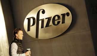 In this Monday, Nov. 23, 2015, file photo, a man enters Pfizer's world headquarters, in New York. Pfizer will not split into two publicly traded companies, a decision that, at least for now, ends Wall Street speculation over the drugmaker's future. The company believes it is best positioned to maximize shareholder value in its current form, but said Monday, Sept. 26, 2016, that it's reserving the right to split in the future if the situation changes. (AP Photo/Mark Lennihan, File)