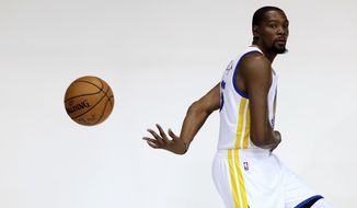 Golden State Warriors forward Kevin Durant poses for photos during NBA basketball media day Monday, Sept. 26, 2016, in Oakland, Calif. (AP Photo/Marcio Jose Sanchez)