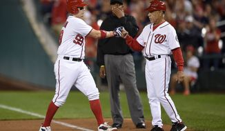 Washington Nationals' Jose Lobaton, left, fist bumps first base coach Davey Lopes, right, as he stands on first with a single during the sixth inning of a baseball game against the Arizona Diamondbacks, Tuesday, Sept. 27, 2016, in Washington. (AP Photo/Nick Wass)