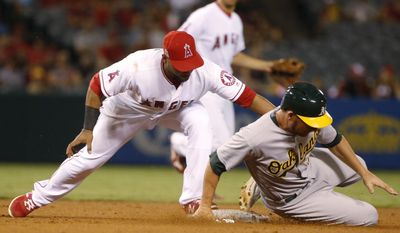 Oakland Athletics' Danny Valencia steals second base as Los Angeles Angels shortstop Andrelton Simmons applies a late tag during the fifth inning of baseball game Monday, Sept. 26, 2016, in Anaheim, Calif. (AP Photo/Lenny Ignelzi)