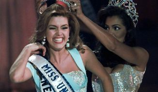 In this May 17, 1996, file photo, the new Miss Universe Alicia Machado of Venezuela reacts as she is crowned by the 1995 winner Chelsi Smith at the Miss Universe competition in Las Vegas. Machado became a topic of conversation during the first presidential debate between Republican nominee Donald Trump and Democratic candidate Hillary Clinton on Sept. 27, 2016. (AP Photo/Eric Draper, File)