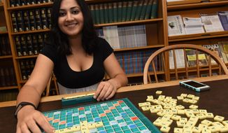 In this Sept. 22, 2016, photo, Nitya Chagti, a student of Juniata College, poses for a photo with Scrabble board game at the college in Huntingdon, Pa. The international-level Scrabble competitor was ranked among the top 20 competitors at the international GAIL cup in Delhi, India, in July. (J.D. Cavrich/Altoona Mirror via AP)