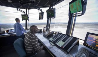 FAA Air Traffic Controllers work in the Dulles International Airport Air Traffic Control Tower in Sterling, Va., Tuesday, Sept. 27, 2016. Data Comm is now operational at the Dulles International Airport and gives air traffic controllers and pilots the ability to transmit flight plans, clearances, instructions, advisories, flight crew requests, and reports via a digital message service. (AP Photo/Cliff Owen)