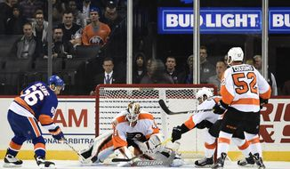 New York Islanders center Josh Ho-Sang (66) shoots the puck past Philadelphia Flyers goalie Anthony Stolarz, defenseman Will O'Neill (45) and center Nick Cousins (52) to score a goal in the third period of a preseason NHL hockey game in New York., Monday, Sept. 26, 2016. The Islanders won 3-0. Pleased with the progress made during the Islanders' first season in Brooklyn, Brett Yormark, the Chief Executive Office for Brooklyn Sports and Entertainment, is looking forward to the team's second year at Barclays Center. (AP Photo/Kathy Kmonicek)