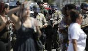 """People block streets during a protest Wednesday, Sept. 28, 2016, in El Cajon, Calif. Dozens of demonstrators on Wednesday protested the killing of a black man shot by an officer after authorities said the man pulled an object from a pocket, pointed it and assumed a """"shooting stance."""" (AP Photo/Gregory Bull)"""