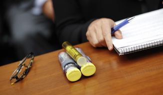 In this Sept. 21, 2016 file photo, EpiPens brought by Mylan CEO Heather Bresch are seen on Capitol Hill in Washington as she testified before the House Oversight Committee hearing on EpiPen price increases. (AP Photo/Pablo Martinez Monsivais, File)