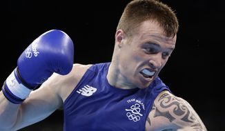 "FILE - In this file photo dated Sunday, Aug. 7, 2016, Ireland's Steven Donnelly, fights Algeria's Zohir Kedache during a men's welterweight 69-kg boxing match at the 2016 Summer Olympics in Rio de Janeiro, Brazil. The International Olympic Committee (IOC) has sanctioned three boxers Wednesday Sept. 28, 2016, including Donnelly, issuing ""severe reprimands"" for violating the rules that prohibit betting on fights at the Olympics in Rio de Janeiro. None of the boxers won medals and the IOC says ""there was no intent to manipulate any event."" (AP Photo/Frank Franklin II, FILE)"