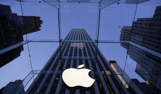 FILE - In this Sept. 5, 2014, file photo, the Apple logo hangs in the glass box entrance to the company's Fifth Avenue store in New York. On Wednesday, Sept. 28, 2016, Apple announced it is extending its push into selling business technology by forging a partnership with the Deloitte consulting firm to advise companies on using iPhones, iPads and Apple software in the workplace. (AP Photo/Mark Lennihan, File)