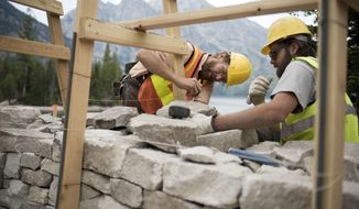 In this Aug. 18, 2016 photo, Ray Haas, left, with Dry Stone Conservancy, works with Grand Teton trail crew member Justin Williams on one of two stone parapet overlooks under construction on the southeast shore of Jenny Lake as part of a five-year restoration project in Grand Teton National Park near Moose, Wyo. The trail is the most popular and heavily-used in the park. (Bradly J. Boner/Jackson Hole News & Guide via AP)
