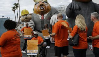 FILE - In this Sept. 21, 2016 file photo, Laborers' International Union of North America members and Culinary Union members walk by an inflatable figure depicting Donald Trump during a protest outside of the Trump International hotel, in Las Vegas. The unions were protesting what they say is an anti-union stance by the hotel. Union members are calling the public to boycott Republican presidential nominee Trump's businesses nationwide because he isn't negotiating a contract with the more than 500 eligible workers at his high-rise Las Vegas hotel. (AP Photo/John Locher, File)